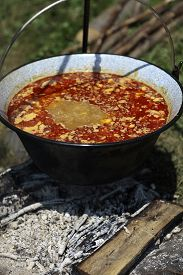 picture of smut  - Delicious fresh ukrainian hot red borsch in enamelled kettle is cooked on fire with sour cream outdoor picnic closeup vertical picture - JPG