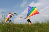 foto of exaltation  - Children flying rainbow kite in the meadow on a blue sky background - JPG