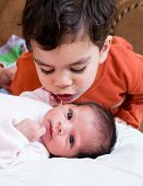 image of east-indian  - A young boy talking to his newborn sister - JPG