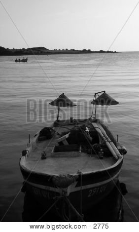 Picture or Photo of A small boat for night fishing - with lights. Black and white photo, angle of the sun called for it...