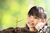 A Girl Planting Young Plant On Soil With A Hope Of Good Environment poster