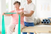 Senior Exercising With A Resistance Band Supported By A Physiotherapist poster