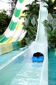 Head Of Man Coming Down On The Slide Make The Water Splashing In The Aqua Park , Water Park Resort.  poster