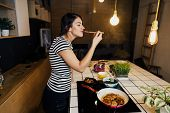 Young Woman Cooking A Healthy Meal In Home Kitchen.making Dinner On Kitchen Island Standing By Induc poster