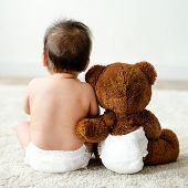 Back of a baby with a teddy bear poster