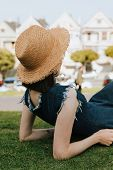 Woman relaxing on the grass near the San Francisco, USA poster