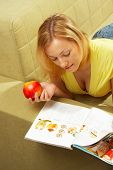 The Girl Lays On A Sofa, Reads The Cooking Magazine And Eats An Apple poster