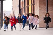 A happy multi-ethnic group of young school kids wearing coats and carrying schoolbags running in a w poster