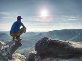 Man Risk At The Edge. Man In Training Sports Clothes  Sit On Cliff And Enjoying Far View. View Into  poster