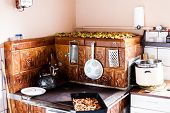 Old Traditional Oven With Ceramic Tiles. Kitchen Utensils Handeg On The Old Oven. Old Teapot On The  poster