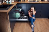 Beautiful young woman frustrated with dishes in a modern kitchen with dishwasher poster