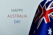 closeup of some australian flags and the text happy australia day against an off-white background poster