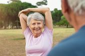Smiling senior woman looking at man while doing arm stretching exercise. Old man in conversation wit poster