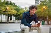 Mature businessman sitting on bench and using smart phone at dusk. Happy smiling guy in smart casual poster