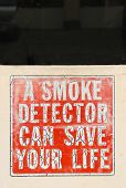 picture of smoke detector  - This is an old smoke detector sign on the front man door to an old fire station - JPG
