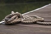 A Thick Rope Tied Into A Sailor's Knot By The Harbor