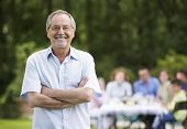 foto of spectacles  - Portrait of senior man with arms crossed and family having lunch in background - JPG