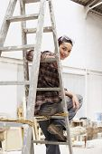 Portrait of happy young female painter sitting on ladder in work site