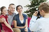 Young boy taking photo of sitter, mother and father by Christmas tree