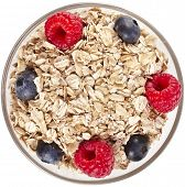 oat flake in a bowl with fresh berries surface top view, diet concept isolated on white background