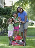 Mother and daughters pushing lawn mower