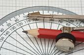stock photo of protractor  - plastic protractor and compass on graph paper - JPG