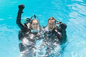 stock photo of oxygen mask  - Smiling couple on scuba training in swimming pool looking at camera on a sunny day - JPG