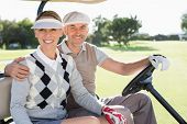stock photo of buggy  - Happy golfing couple driving in their buggy smiling at camera on a sunny day at the golf course - JPG