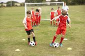 stock photo of little-league  - Junior football team training with coach - JPG