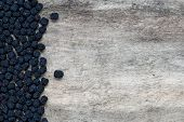 picture of aronia  - Healthy organic dried aronia berries on old wooden background - JPG