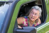 stock photo of blood drive  - Angry senior woman driver with road rage yelling out car window - JPG