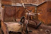 picture of tricycle  - Old and broken tricycle on a rusted World War Two Universal Carrier - JPG