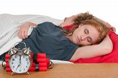 image of time-bomb  - Young couple sleeping in bed with a time bomb alarm clock - JPG