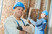 picture of millwright  - cheerful plasterer worker at a indoors wall insulation works - JPG