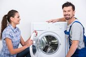 picture of washing-machine  - Repairman is repairing a washing machine for housewife - JPG