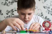 picture of pre-teen boy  - a Teen boy at home with electronic project - JPG