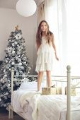 picture of preteen  - Preteen child girl wake up and jumping on her bed near decorated Christmas tree in beautiful hotel room in the holiday morning - JPG