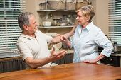 stock photo of argument  - Senior couple having an argument at home in the kitchen - JPG
