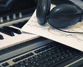 Постер, плакат: Наушники и ноты на клавиатуре