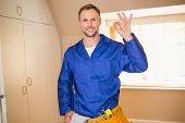 picture of handyman  - Handyman smiling at camera in tool belt in a new house - JPG