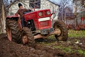 pic of plowing  - Senior farmer on an old red tractor plowing his garden in the backyard  - JPG