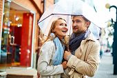 foto of amor  - Amorous valentines standing under umbrella in urban environment - JPG