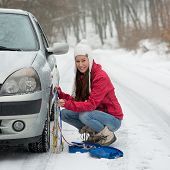 stock photo of breakdown  - Woman putting winter tire chains on car wheel snow breakdown - JPG