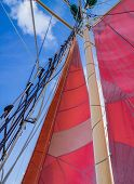 stock photo of sail ship  - Red Sails Mast and Ships Rigging on Schooner Sailing Ship - JPG