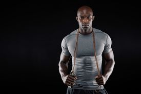 picture of roping  - Handsome muscular man posing with jumping rope on black background - JPG