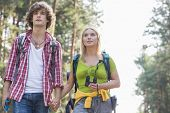 stock photo of walking away  - Young couple looking away while hiking in forest - JPG