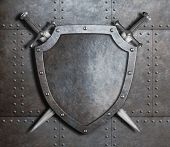 image of crossed swords  - metal shield and two crossed swords over armor plates metal background - JPG