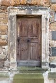 foto of stepping stones  - Old, brown, weathered wooden door with old door handle and centered doorknob made of metal in a stone portal. In front are two steps.