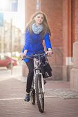 picture of cobblestone  - woman drives on bike on cobblestone in city - JPG