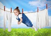 picture of laundry  - Funny child hanging on line with clothes laundry creative concept - JPG